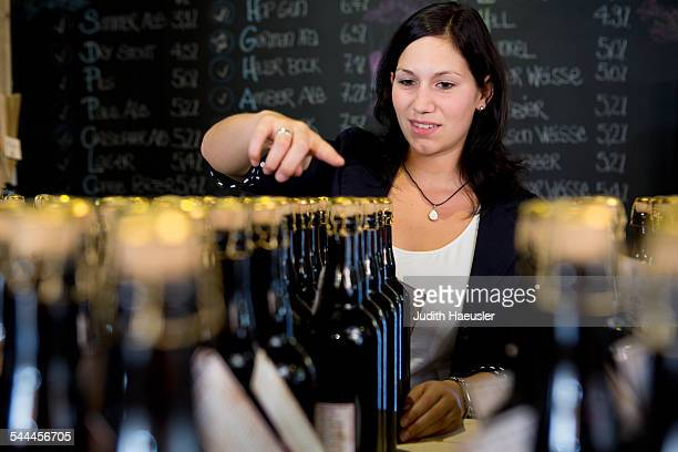 Woman counting bottles of wine in shop
