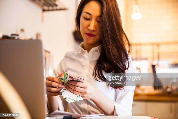 Woman counting cash at home