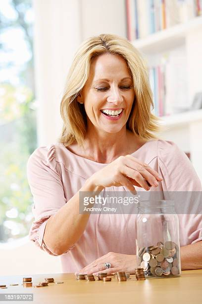 woman counting coins into jar - 40 44 jaar stock pictures, royalty-free photos & images