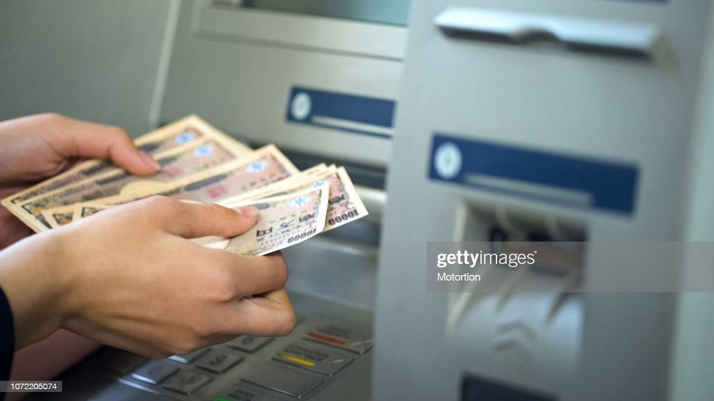 Woman counting Japanese Yen withdrawn from ATM, 24 hours service, easy banking : Stock Photo