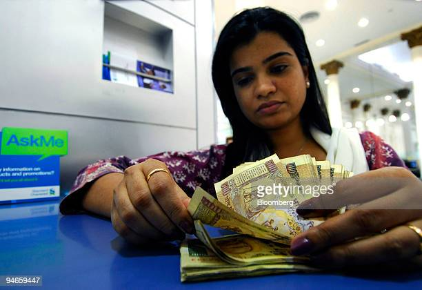A woman counts 500 Indian rupees notes at a Standard Chartered Bank branch in Mumbai India on Thursday Nov 29 2007 India's economy grew last quarter...