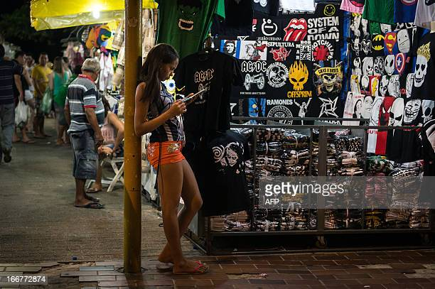 A woman counts her sales at night street fair besides the waterfront street in Fortaleza state of Ceara in northeastern Brazil on April 16 2013 AFP...