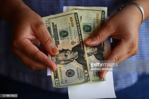 Woman counts money outside a U.S. Remittance collection agency in San Isidro, 70 km northeast of San Salvador, on June 10 amid the new coronavirus...