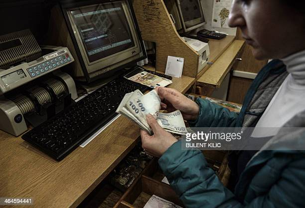 A woman counts Turkish lira banknotes at a currency exchange office in Istanbul on January 23 2014 The beleaguered Turkish lira recovered from...