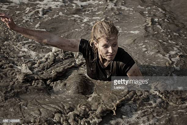woman covered by mud crossing the canal