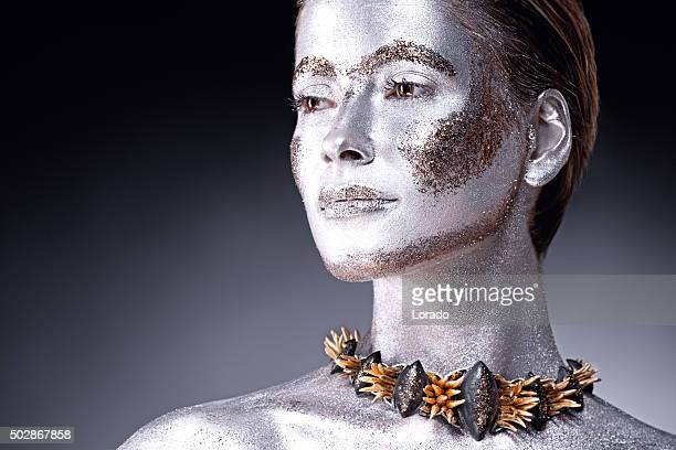 woman covered by sliver paint wearing luxury jewellery