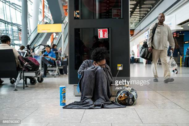 A woman covered in a blanket sleeps in Heathrow Airport Terminal 5 on May 28 2017 in London England Thousands of passengers face a second day of...