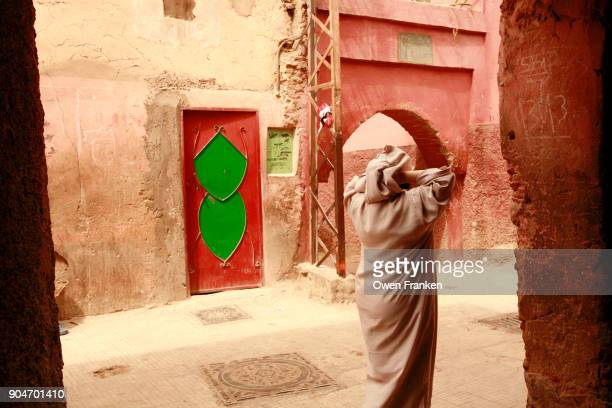 woman covered in Arab style walking through the back streets of Marrakech, Morocco
