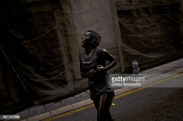 Woman covered in black grease shouts during the traditional festivities of the Cascamorras, in Baza, near Granada, on September 6, 2015. Every year...