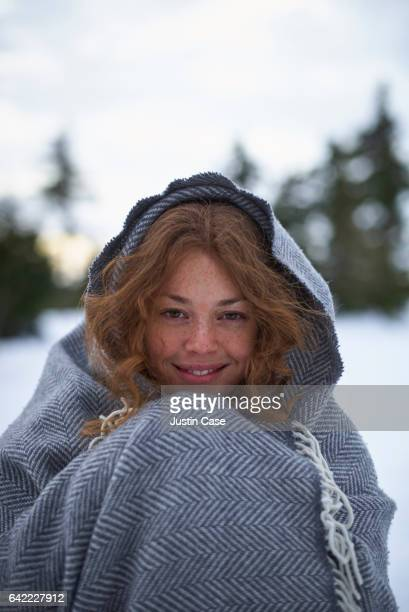 woman covered in cashmere blanket in winter