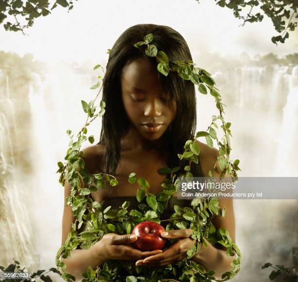 woman covered in vines holding apple - temptation of eve stock-fotos und bilder