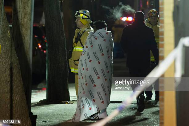 A woman covered with a Red Cross blanket talks to a fire fighter during a major house fire on Prospect avenue on December 28 2017 in the Bronx...