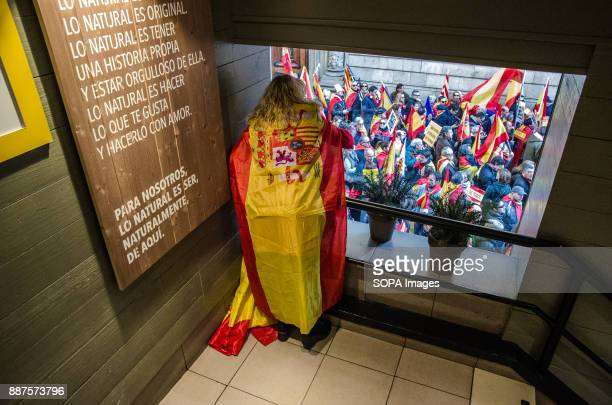 A woman covered with a Spanish flag seen taking photos of the demonstration from the inside of a café Spain celebrates today the 39 anniversary of...