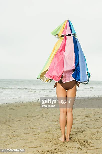 Woman covered with beach umbrella standing on beach
