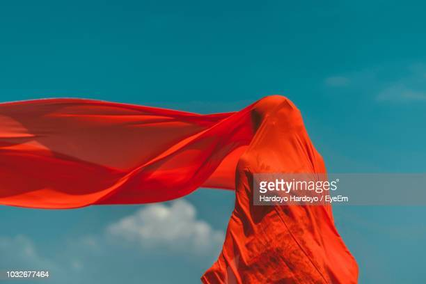 woman covered with red fabric while standing against sky - indonesian cloth 個照片及圖片檔