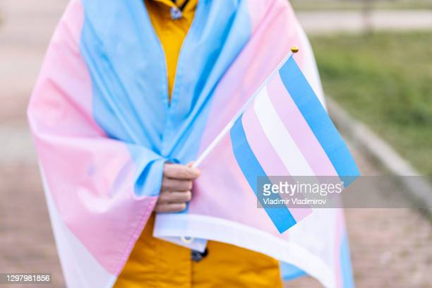 woman covered with the transgender flag on a protest - transgender stock pictures, royalty-free photos & images