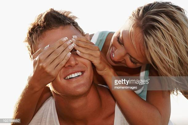 Woman covering boyfriend's eyes