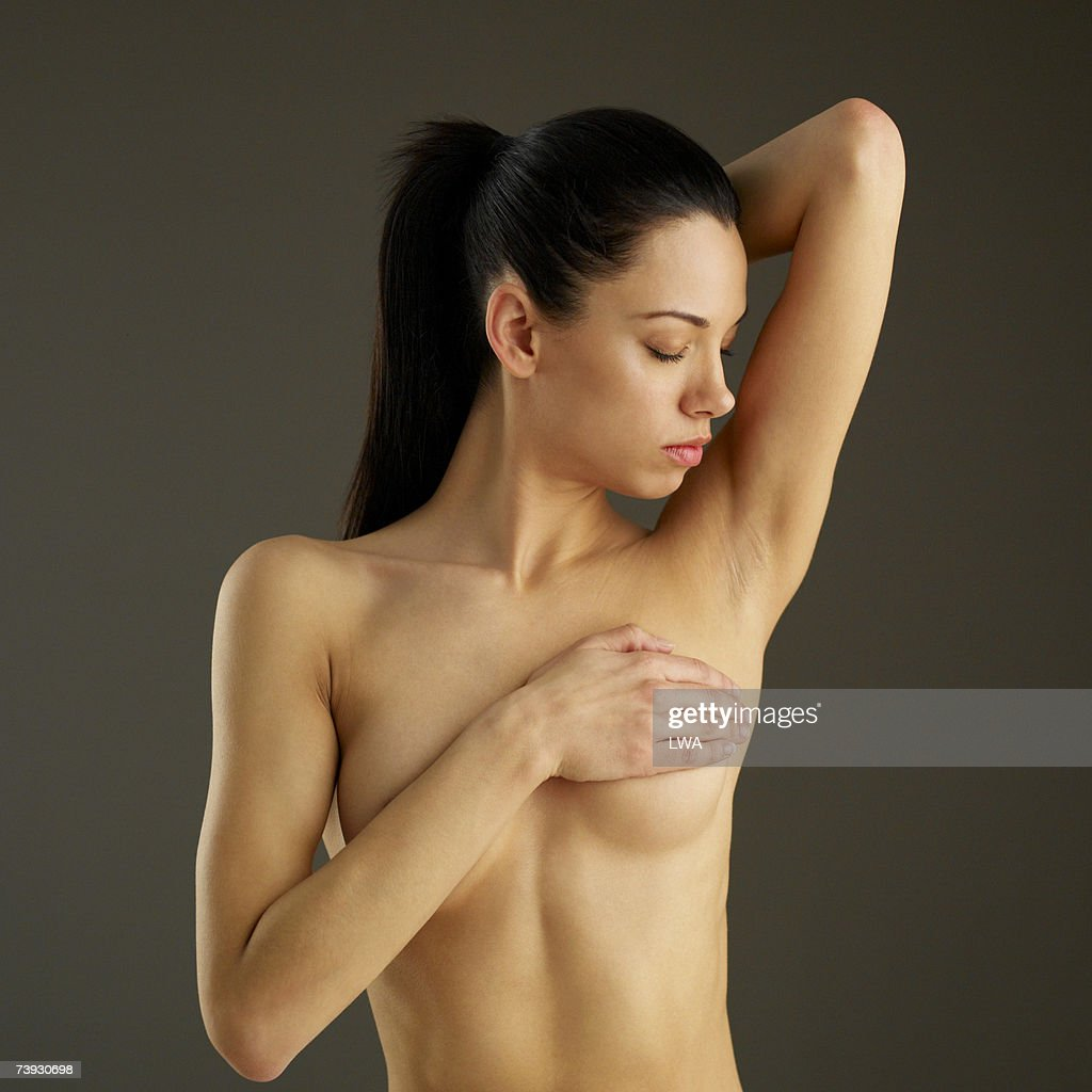 Woman covering breast with hand with arm raised, waist up : Stock Photo