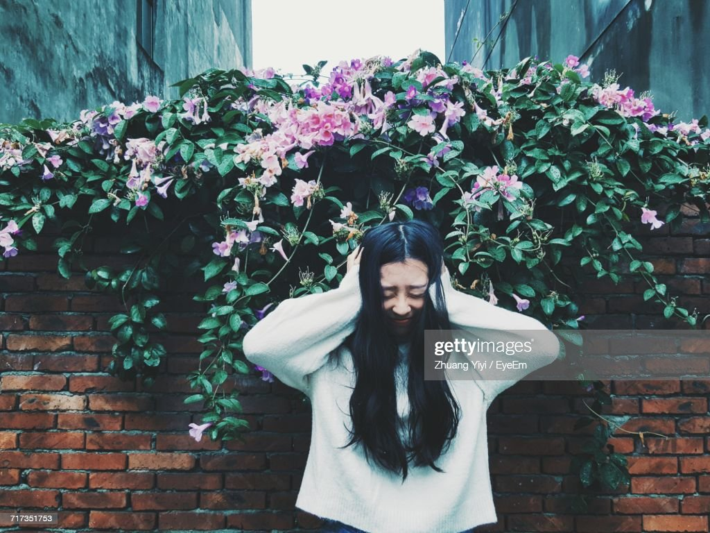 Woman Covering Ears While Standing Against Plants And Brick Wall In Yard : Stock Photo