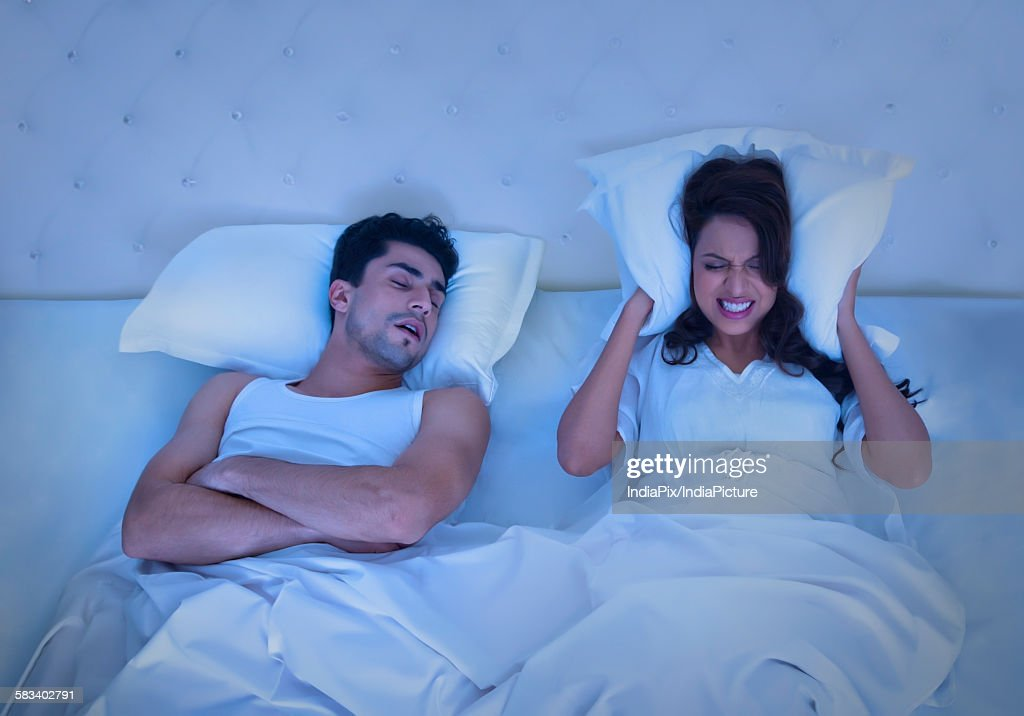 Woman covering ears with pillow while man snores : Stock Photo
