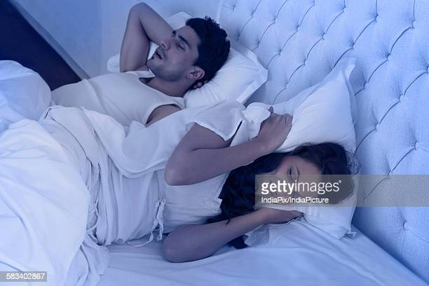 Woman covering ears with pillow while man snores
