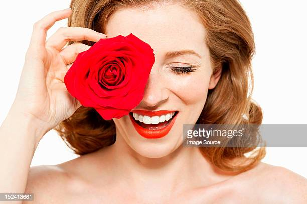Woman covering eye with red rose