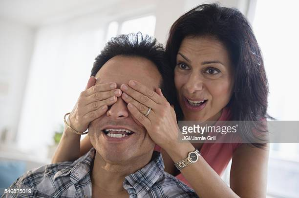 Woman covering eyes of husband