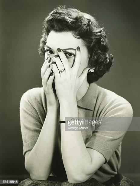 Woman covering face, peeping through fingers, (B&W)