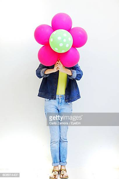 Woman Covering Face With Artificial Flower Against White Background