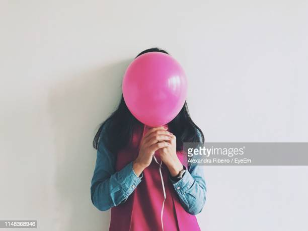 woman covering face with balloon standing against wall - covering stock pictures, royalty-free photos & images