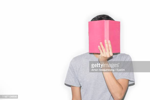 woman covering face with book against white background - obscured face stock pictures, royalty-free photos & images