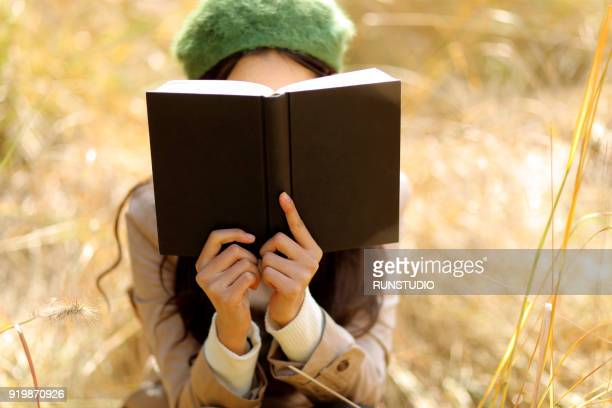 Woman covering face with book in autumn park
