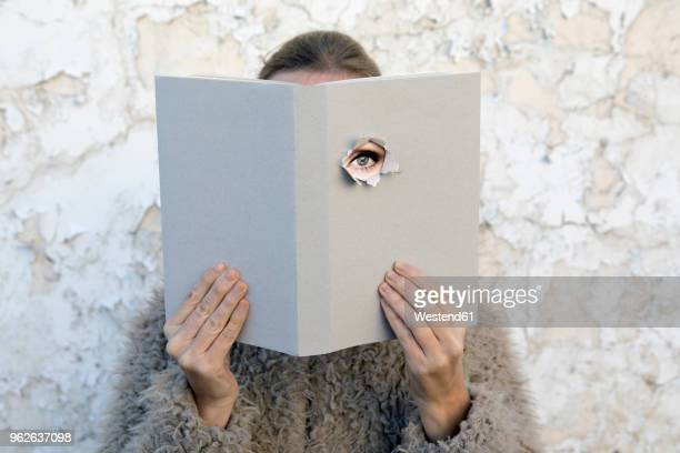 woman covering face with book, reading poetry, eye looking through cover - big brother orwellian concept stock pictures, royalty-free photos & images
