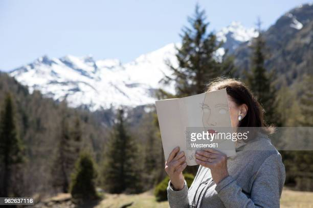 Woman covering face with book, reading poetry in the mountains