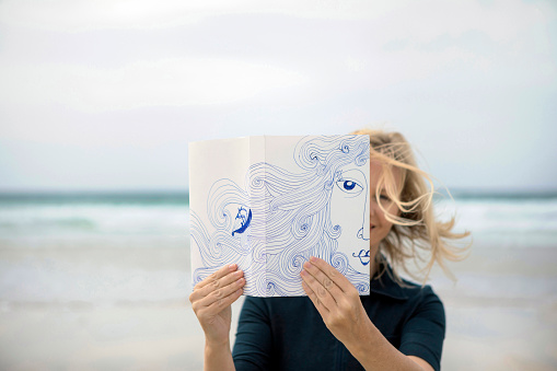 Woman covering face with book, reading poetry on beach - gettyimageskorea