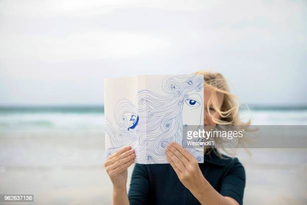 woman covering face with book, reading poetry on beach - obscured face stock pictures, royalty-free photos & images
