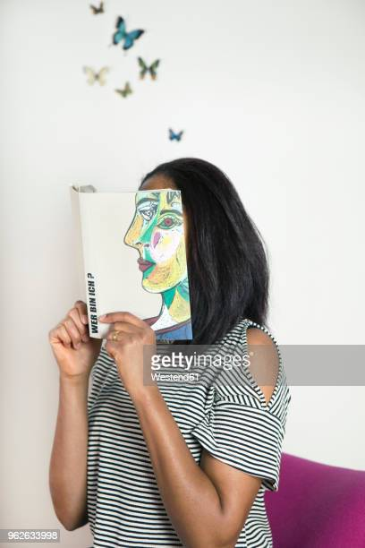 Woman covering face with book, reading poetry with butterflies