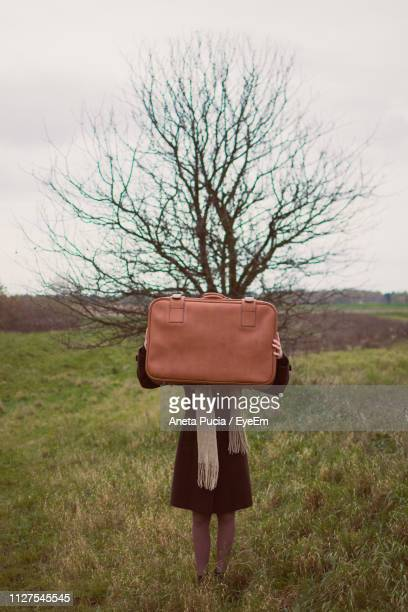 Woman Covering Face With Briefcase On Field Against Sky