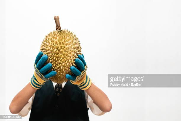 woman covering face with durian against white background - durian stock pictures, royalty-free photos & images