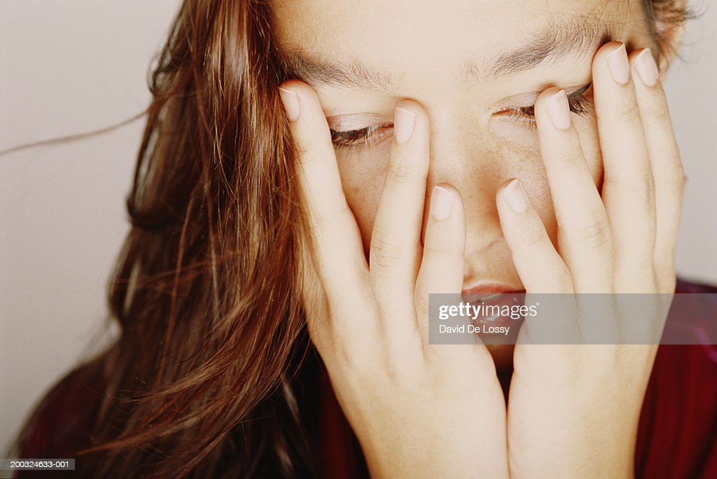 Woman covering face with hands, looking down : Stock Photo