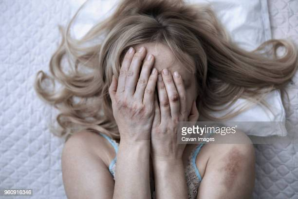 woman covering face with hands while lying on bed at home - violencia intrafamiliar fotografías e imágenes de stock