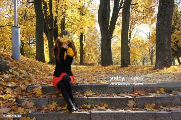 Woman Covering Face With Maple Leaves On Steps At Park During Autumn