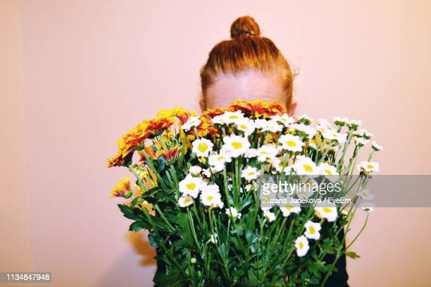 woman covering face with plants against wall - covering stock pictures, royalty-free photos & images