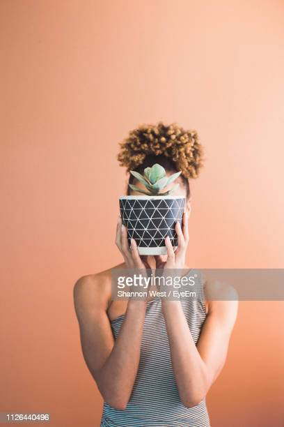 woman covering face with potted plants against orange background - obscured face stock pictures, royalty-free photos & images