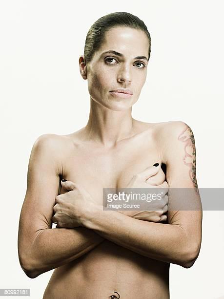 woman covering her breasts - mani su seno foto e immagini stock