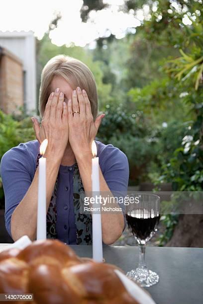 woman covering her face at sabbath dinner - bedekken stockfoto's en -beelden