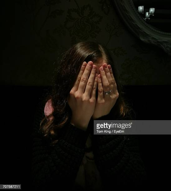 Woman Covering Her Face With Hands In Darkroom
