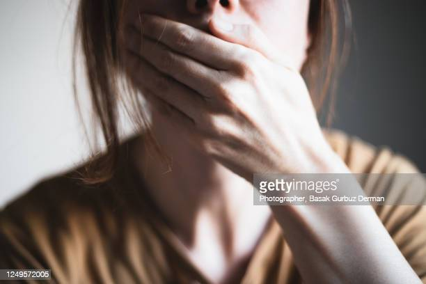 a woman covering her mouth with her hand - facial expression stock pictures, royalty-free photos & images