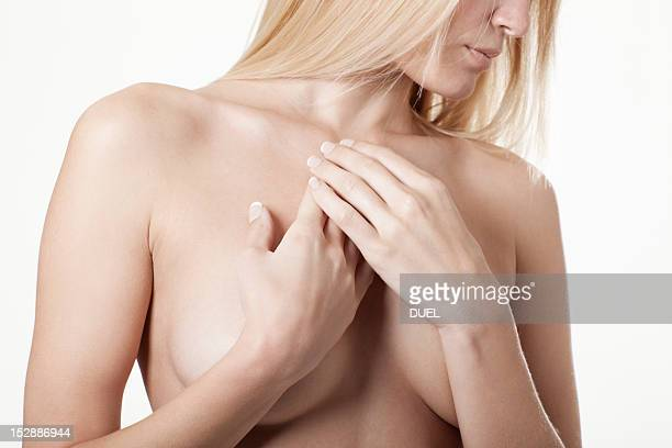 Woman covering her naked breasts