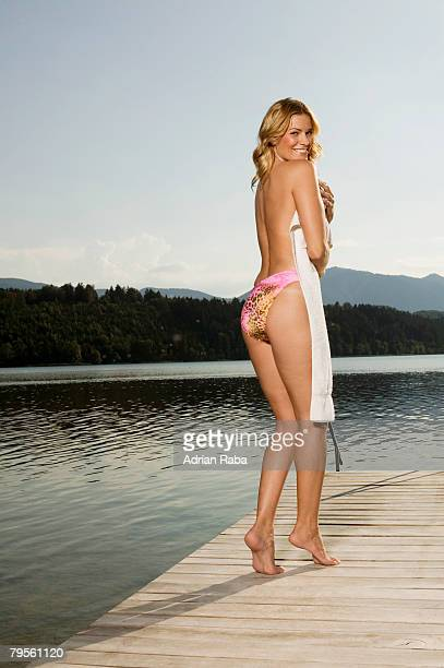 'Woman standing onjetty, covering with towel, rear view'